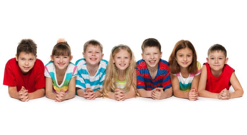 Zeven kinderen die op vloer liggen stock afbeelding