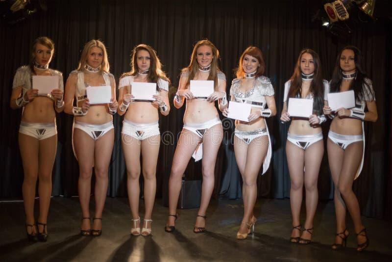 Zeven mooie showgirls in heldere kostuums stock foto