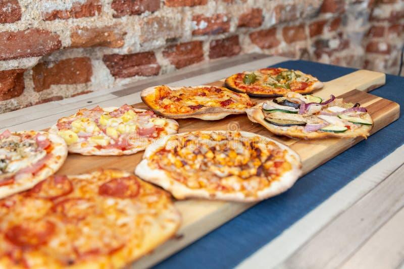 Zeven pizza's op een houten raad, vers uit de oven met nadruk in groentenpizza royalty-vrije stock foto
