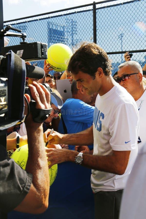 Zeventien keer Grote Slagkampioen Roger Federer die autographs na praktijk voor US Open 2014 ondertekenen stock afbeeldingen