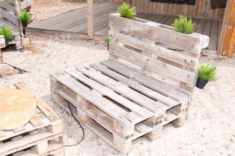 Zewnętrzne ławki robić od starych drewnianych składowych barłogów na piasek plaży barze zdjęcia royalty free