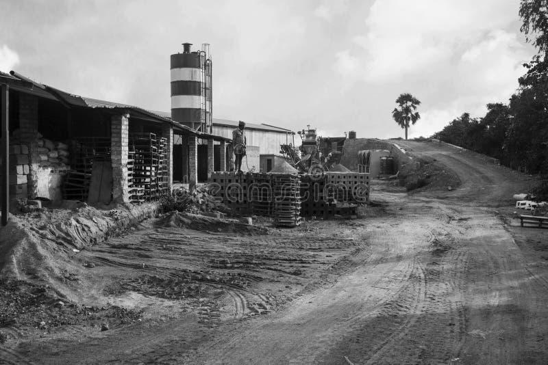 Zewnętrzny widok cementowa fabryka Mężczyzna wodna kiść w Cementowej cegle zdjęcie stock