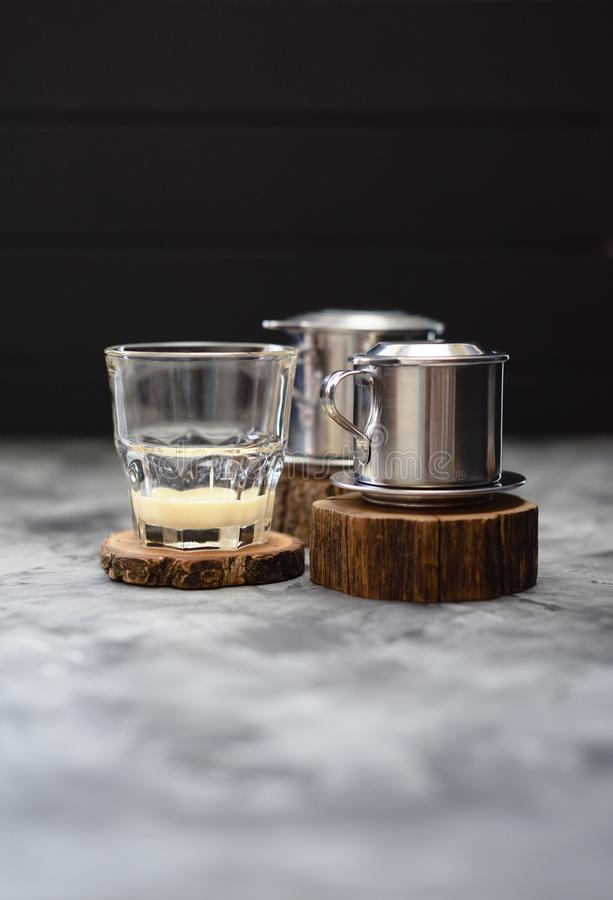 Zgęszczony mleko w szkle gotowym dla robić Wietnamskiej kapinos kawie w kawowego producenta phin na drewnianym cegiełka minimalis zdjęcia royalty free