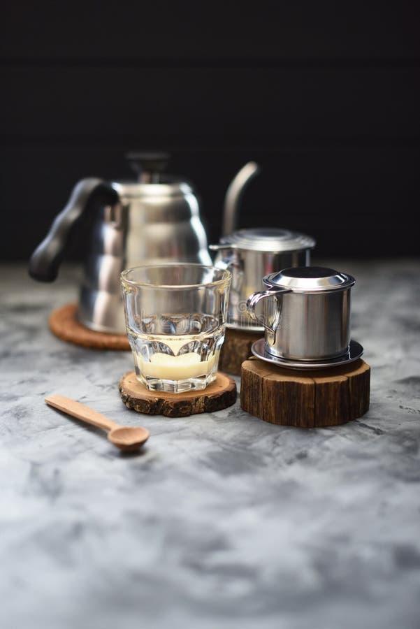 Zgęszczony mleko w szkle gotowym dla robić Wietnamskiej kapinos kawie w phin na drewnianych cegiełkach na ciemnym tle zdjęcie stock