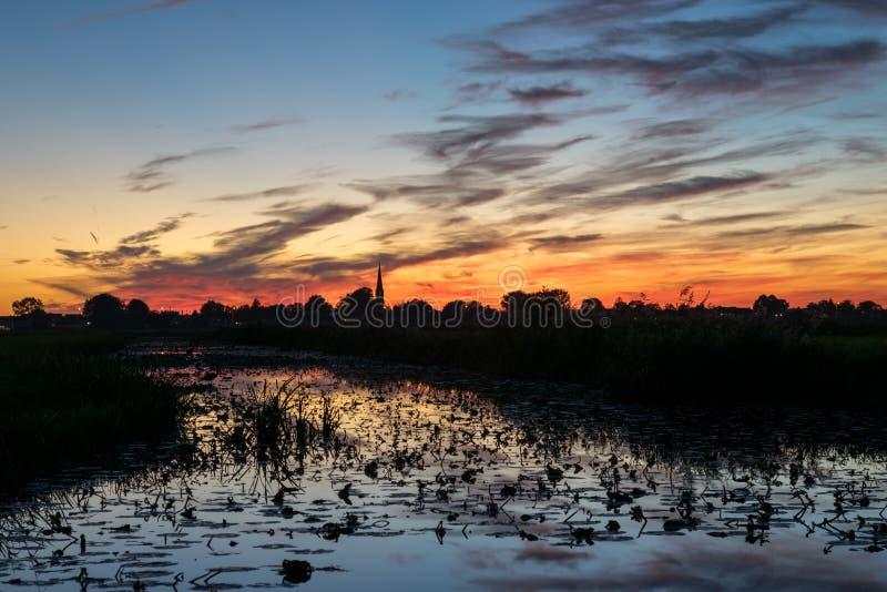 Zgłębia - czerwonego i pomarańczowego niebo z odbiciami w wodzie po zmierzchu obraz royalty free