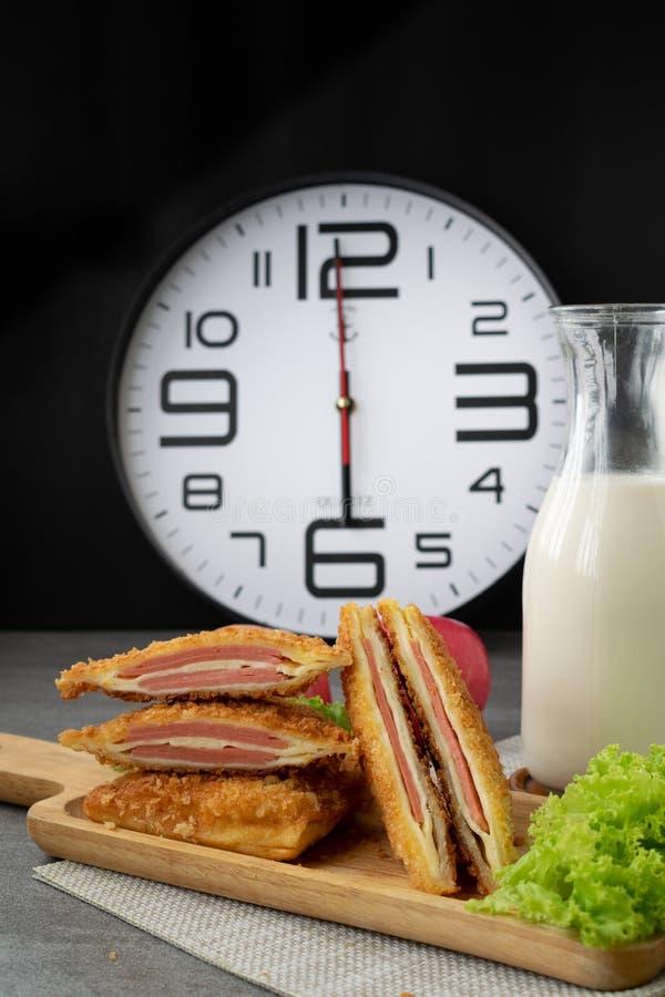 Zgłębiam smażył kanapka faszerującego baleronu ser w drewnianym naczyniu na stole i zegarze zdjęcie stock