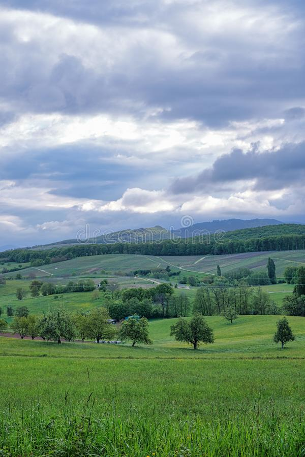 Zgrymaszona wiosna z dramatycznym chmurnym niebem nad obszary trawiaści i wzgórza w Rhine dolinie zdjęcia royalty free