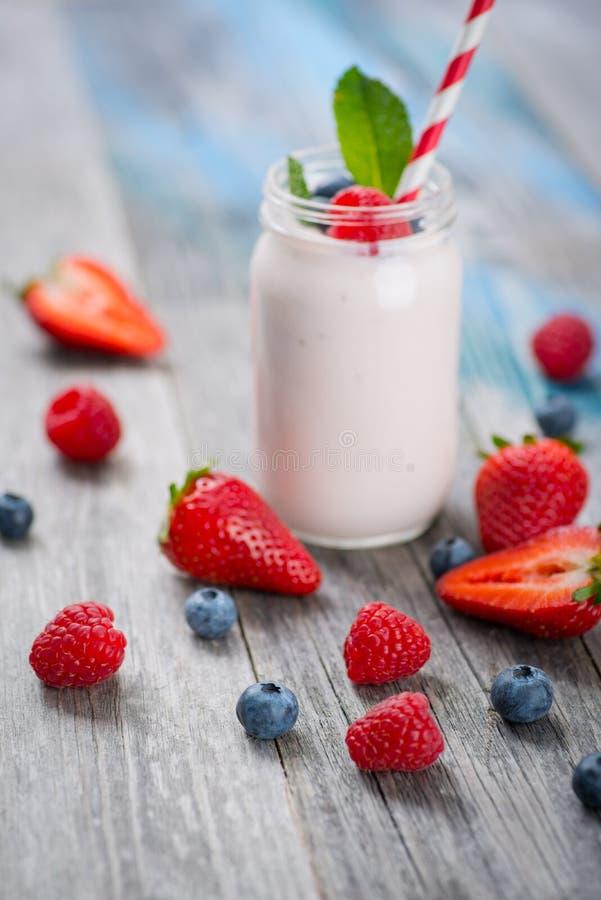 Zgrzyta z pić jogurt, jagody i słomę na drewnianym stole, zdjęcia stock