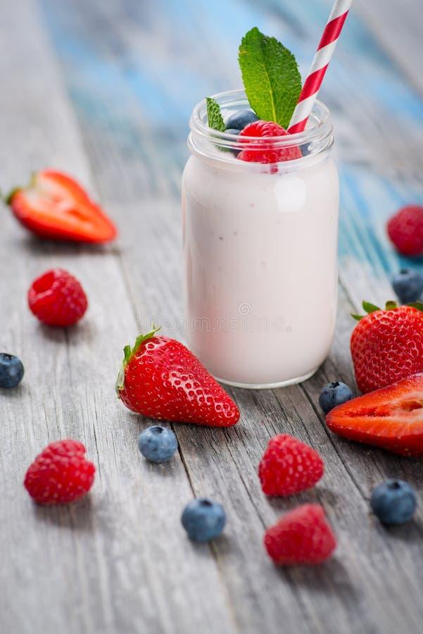 Zgrzyta z pić jogurt, jagody i słomę na drewnianym stole, zdjęcia royalty free