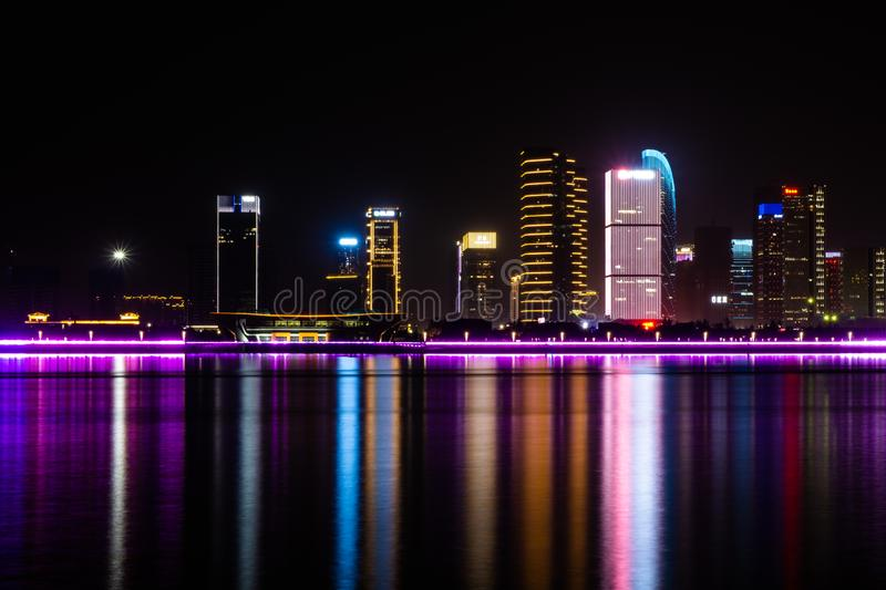 Zhejiang, China - May 21, 2019: Night skyline view of Hangzhou with modern colorful light decoration buildings. And their reflection, is the capital and most stock photo