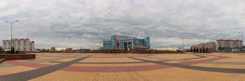 ZHODINO VITRYSSLAND - APRIL 08 2017: Panoramautsikt av den huvudsakliga fyrkanten av staden Slott av kultur av Metallurgists moln arkivfoton