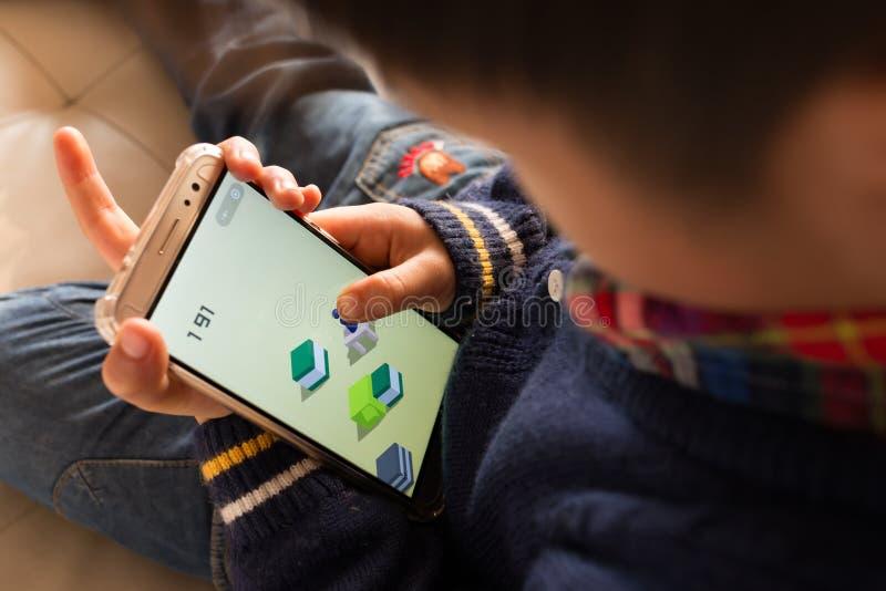 Zhongshan, 22,2018 China-Januari: jong geitje die mobiel spel binnen Wechat spelen door Tencent stock foto's