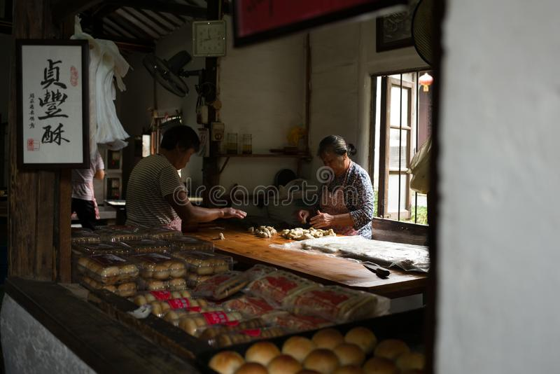 ZHOUZHUANG, CHINA: A food store in traditional cultural styling selling local handmade pastry. Women are in the middle of making h stock images