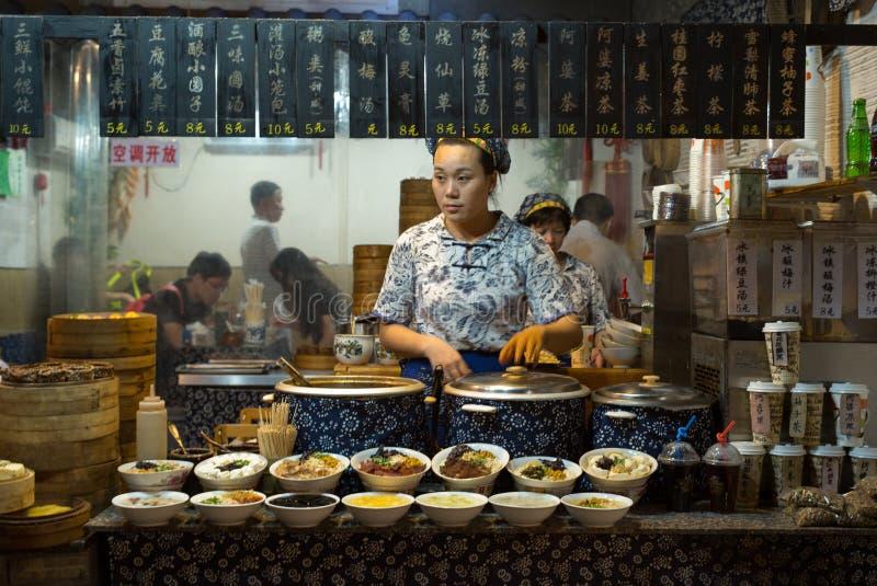 ZHOUZHUANG, CHINA: Una tienda de alimentación en comidas y bebida calientes vendedoras labradoras culturales tradicionales imagen de archivo libre de regalías
