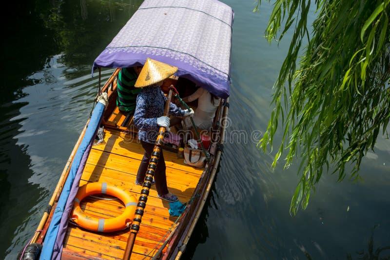 ZHOUZHUANG, CHINY: Helmsman jedzie łódkowatego omijanie przez kanałów obraz royalty free