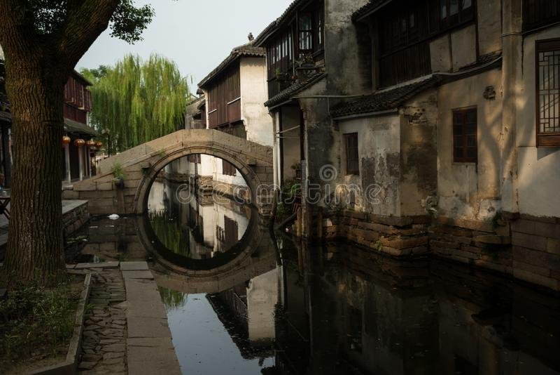 ZHOUZHUANG, CHINY: Starzy domy i bridżowy odbicie w wioska kanale zdjęcie stock