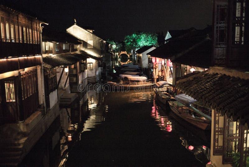 ZHOUZHUANG, CHINY: Starzy domy i bridżowy odbicie w wioska kanale obrazy royalty free