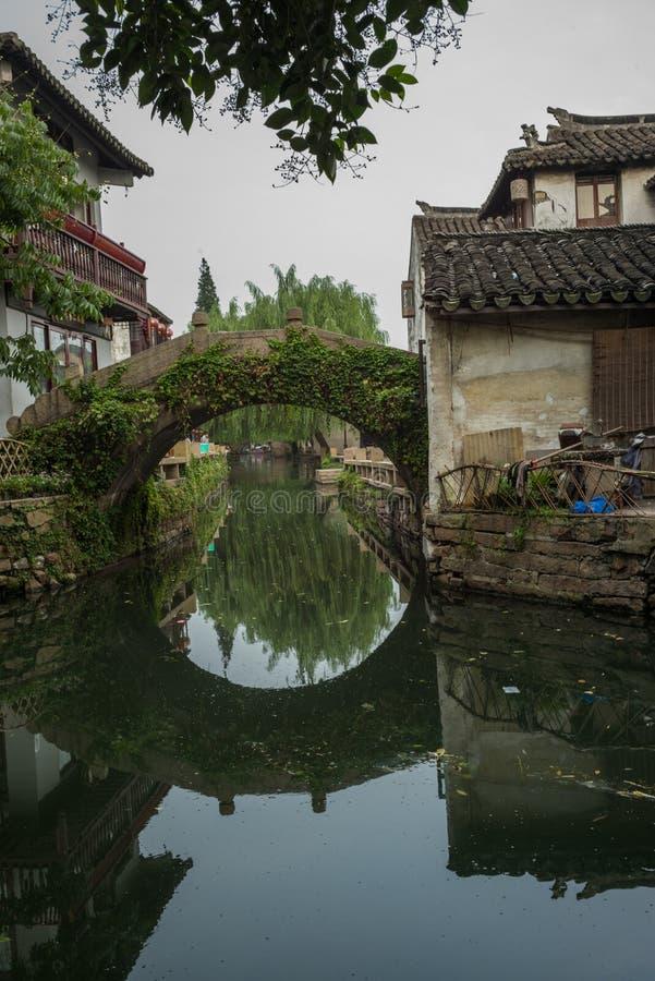 ZHOUZHUANG, CINA: Vecchie case e riflessione del ponte in un canale del villaggio immagine stock