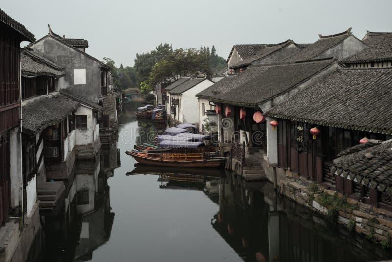 ZHOUZHUANG, CINA: Vecchie case e riflessione della barca in un canale del villaggio immagini stock libere da diritti
