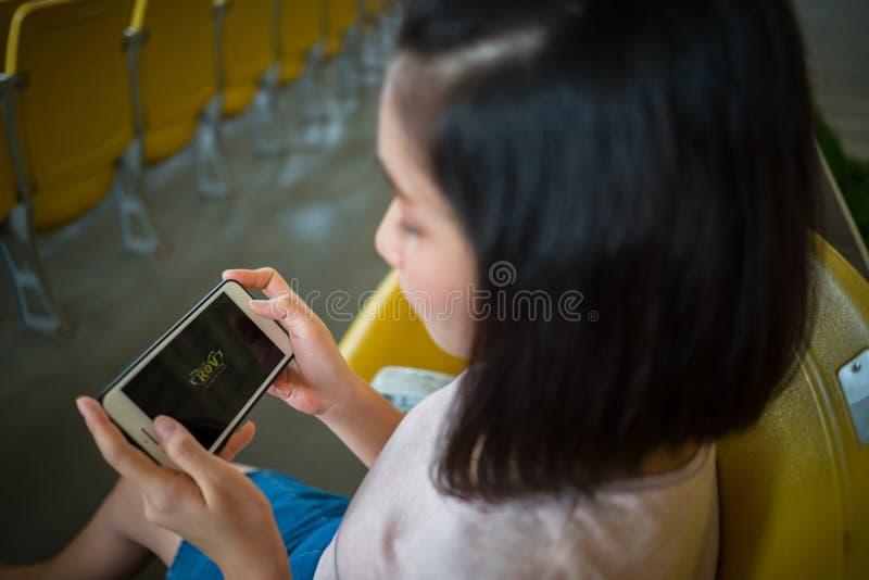 ZHUHAI, CHINA - September 28, 2018: Jonge vrouw die ROV-onli spelen stock afbeelding