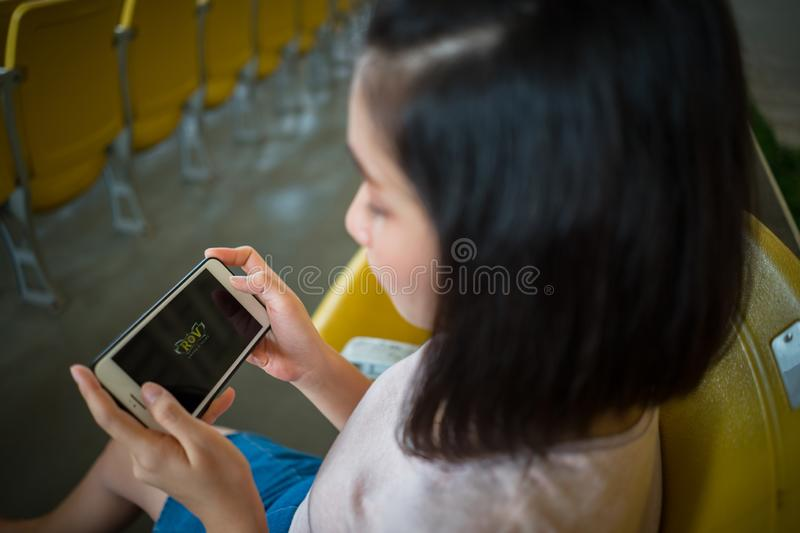 ZHUHAI, CHINA - September 28, 2018: Young woman playing ROV online computer game on smartphone. stock image