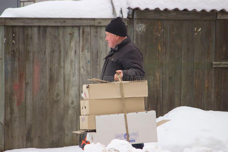 Zhytomyr, de Oekraïne - Januari 8, 2018: Volwassen dakloze mens met karton in de koude winter stock foto's