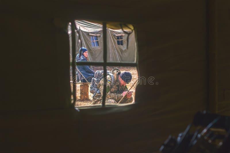 Zhytomyr, de Oekraïne - Maart 5, 2015: De militairen bij een halt maken wapens schoon, bijvullen munitie stock afbeeldingen
