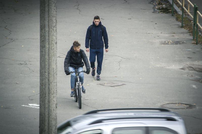 Zhytomyr, Ucrânia - 19 de outubro de 2015: Bicicleta de roda do homem novo no homem de passeio próximo da cidade imagem de stock