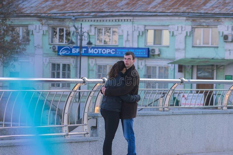 Zhytomyr, Ucrânia - 5 de setembro de 2015: Homem novo e mulher dos pares que abraçam na rua fotografia de stock