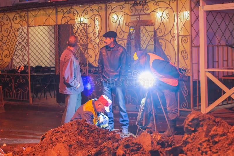 Zhytomyr, Ucrania - 19 de febrero de 2016: Reparación del camino en la ciudad de la noche Trabajadores imagen de archivo libre de regalías