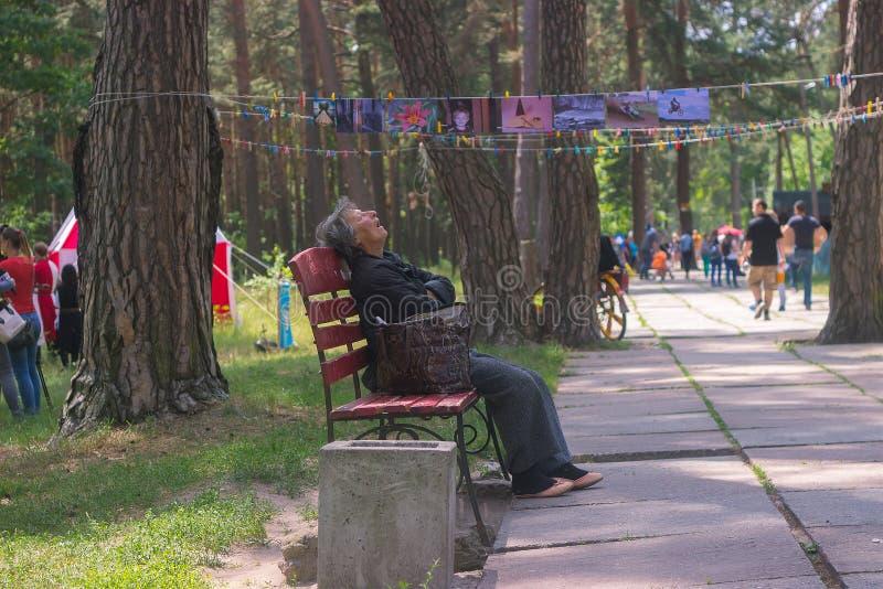 Zhytomyr, Ucrania - 5 de mayo de 2015: Sueño de la mujer mayor de Homless en el banco foto de archivo libre de regalías