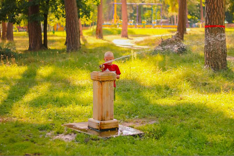 Zhytomyr Ukraina - September 23, 2016: Ung pojke som dricker på en vattenspringbrunn arkivbild