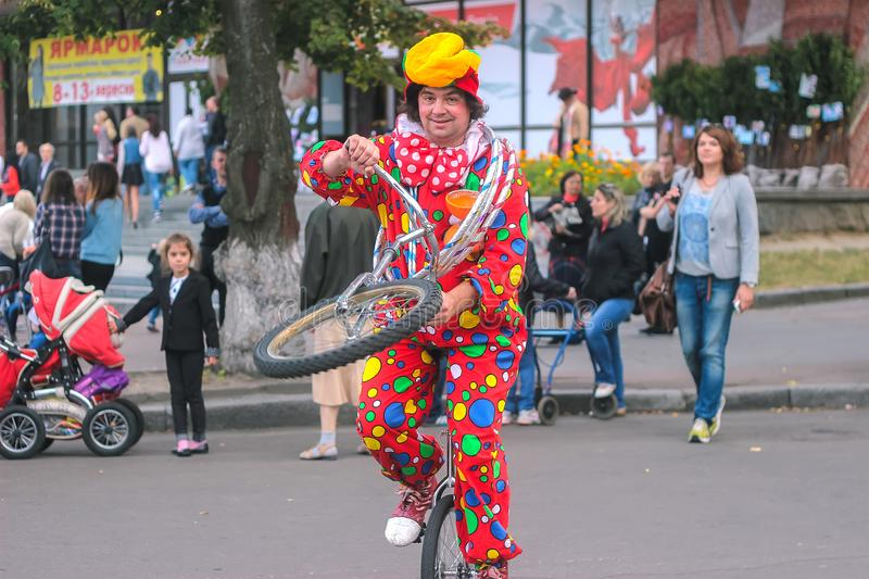 Zhytomyr, Ukraine - September 05, 2015: Clown jumping on unicycle at street stock photography