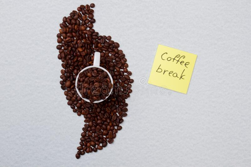 Ziarna kawy starannie uzbrojone wokół kubka zdjęcia stock