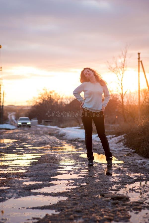 Zich bevindt, vrolijk jong meisje in het platteland op de weg, tijdens het ontdooien van sneeuw stock fotografie