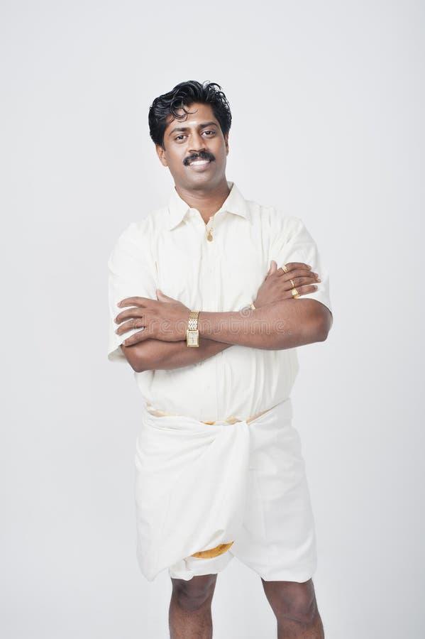 Zich met zijn gekruiste wapens bevinden en zuiden Indische mens die glimlachen royalty-vrije stock fotografie