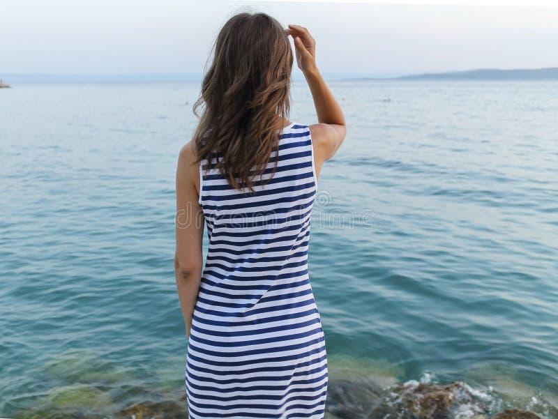 Zich op kust bevinden en meisje die op zee kijken royalty-vrije stock foto's