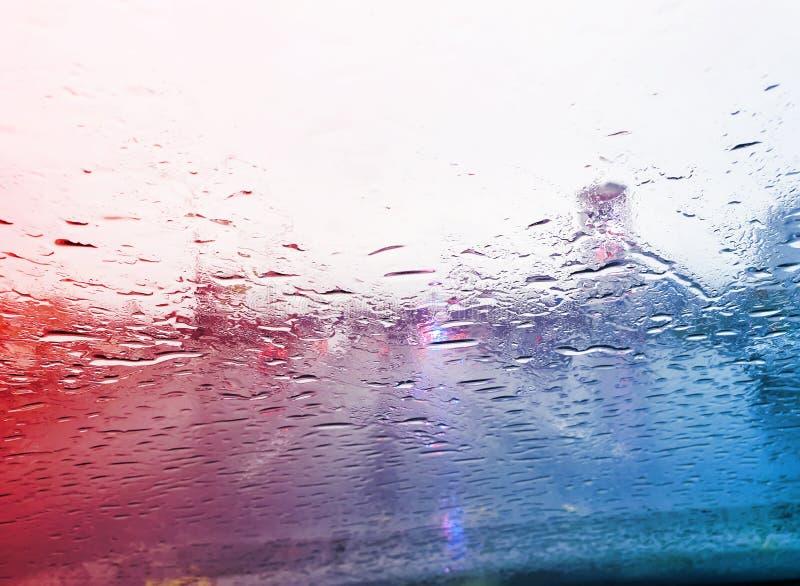 zicht vanuit de auto op raindrops op het raam en de weg met politielichten en silhouetjes van auto ' s die achter hem rijden in d stock afbeelding