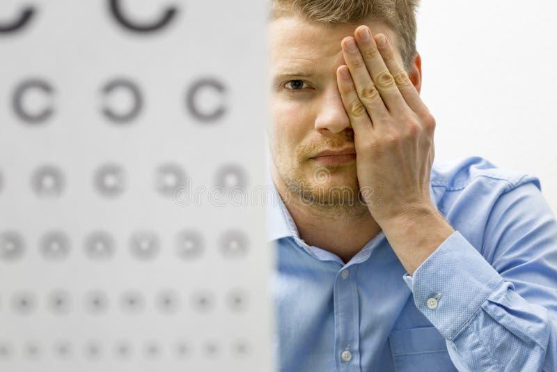 Zichtcontrole mannelijke patiënt onder het onderzoek van de oogvisie stock foto's