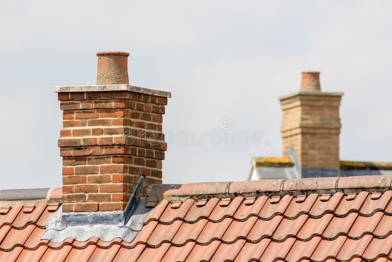 Ziegelsteinkaminstapel auf die moderne zeitgenössische Hausdachoberseite stockfotografie