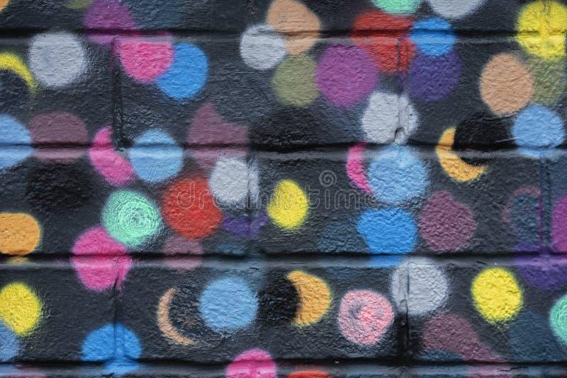 Ziegelsteinwand wird mit hellen abstrakten farbigen Kreisen auf schwarzer Hintergrundnahaufnahme verziert Detail mögen als Graffi lizenzfreie stockbilder