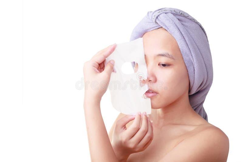 Ziehen asiatisches Gesicht der jungen Frau der Nahaufnahme, das Mädchenentfernen im Gesicht weg der Maske ab, die auf Weiß lokali stockbilder