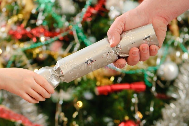 Ziehen eines Weihnachtscrackers stockfotos