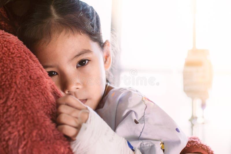 Ziek Aziatisch kindmeisje die IV oplossing koesterend haar moeder hebben royalty-vrije stock afbeelding