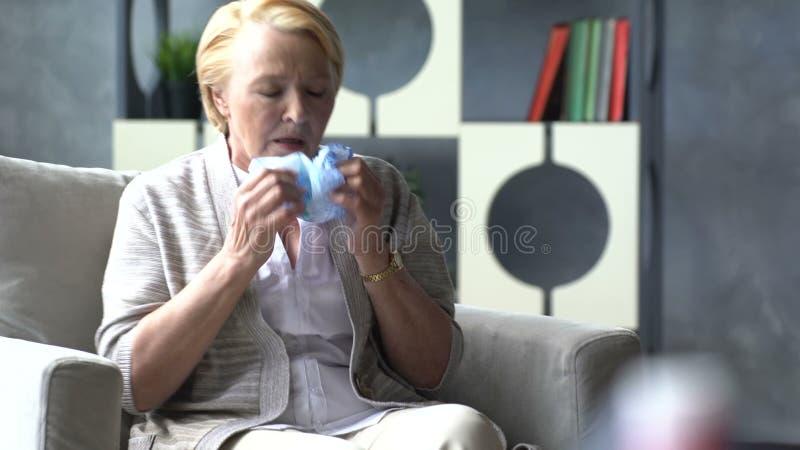 Ziek bejaarde die en hoofd op achtergrond van geneeskundedrug in kop van water houden hoesten