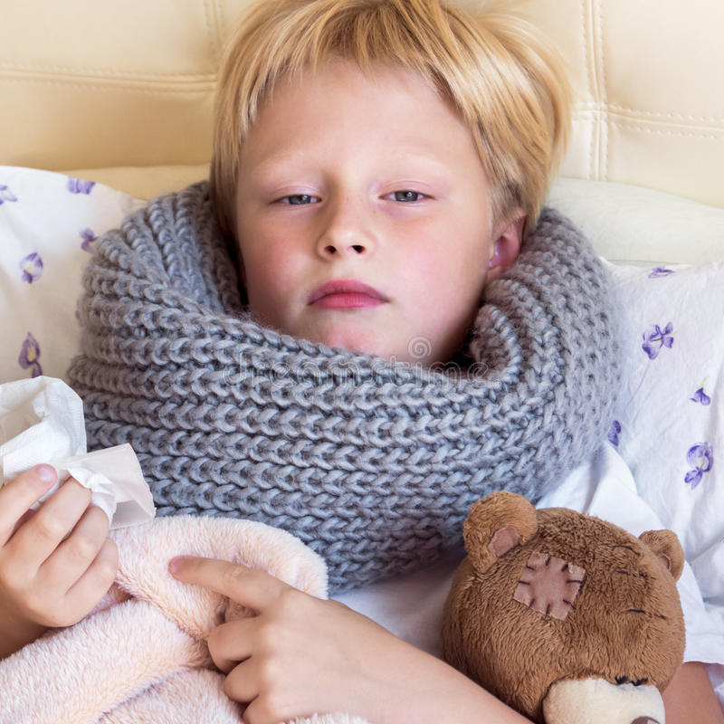 Ziek kind die in bed liggen stock afbeeldingen
