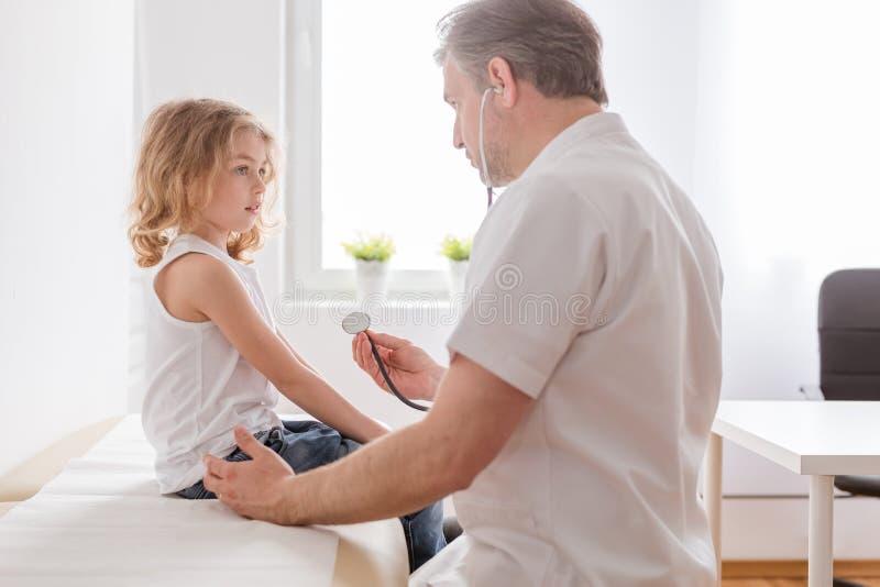 Ziek kind met longontstekingssymptomen en professionele arts in het ziekenhuis stock foto's