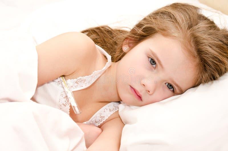 Ziek meisje die in het bed liggen stock afbeelding