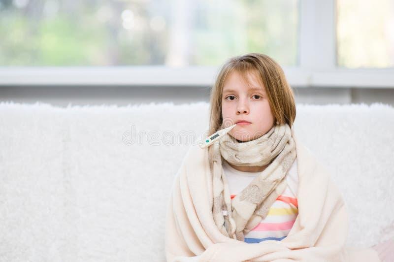 Ziek meisje die met thermometer in mond camera bekijken royalty-vrije stock afbeeldingen
