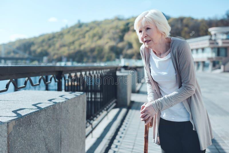 Zieke bejaarde dame die langs riverwalk wandelen langs royalty-vrije stock foto